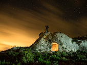 Top of a mountain with an ancient refuge excavated in the rock, a night of sky with clouds orange color and with stars, with a man doing luminous signals with a lantern