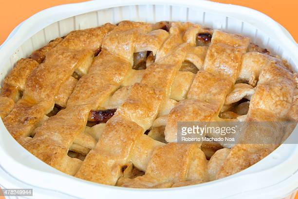 Top of fresh backed apple pie with lattice golden crust resting in white dish on orange background