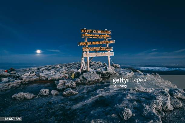 top of mt kilimanjaro with a full moon at sunrise - berg kilimandscharo stock-fotos und bilder