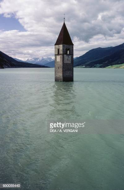 Top of the half-submerged bell-tower in Curon emerging from the waters of Lake Resia, Curon Venosta, Trentino-Alto Adige, Italy, 14th century.