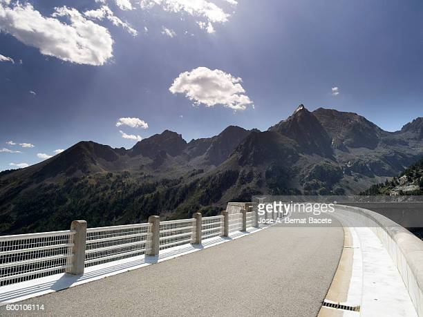 top part of the wall of a dam in the shape of curve, a lake of high mountain,  pyrenees, france - midi pyrénées stock photos and pictures