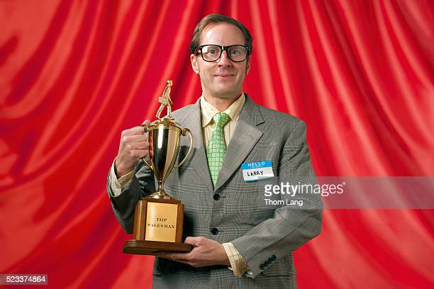 top salesman standing in front of red curtain and holding trophy - trophy stock pictures, royalty-free photos & images