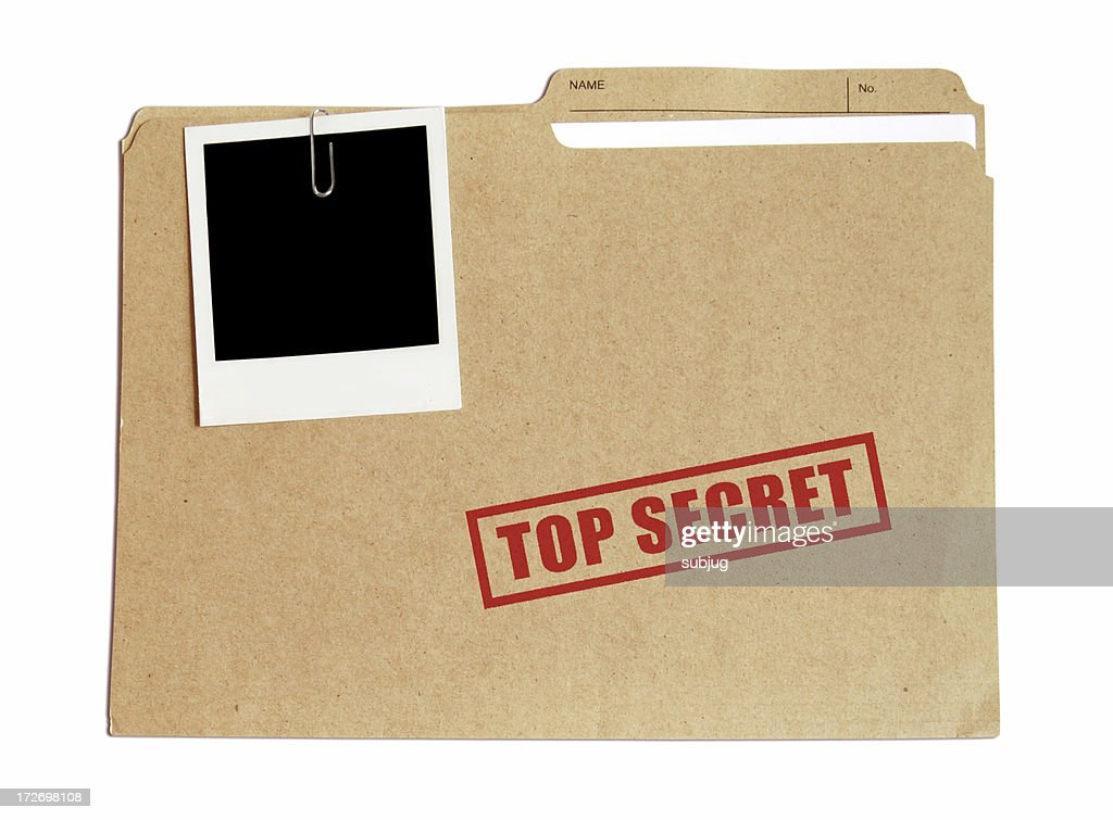 Top secret file in a folder with a Polaroid attached : Stock Photo