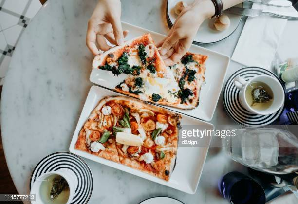 top shot of hands holding and enjoying freshly made pizza slices in the restaurant - 食べ過ぎ ストックフォトと画像