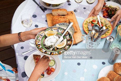 Top shot of table with food, people sharing plates of food.