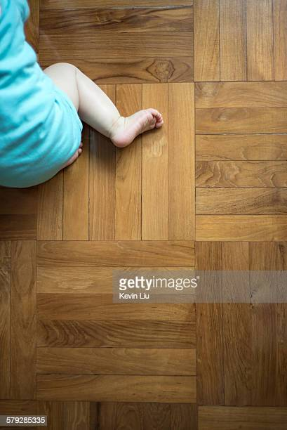 Top shot of wooden floor with baby crawling across