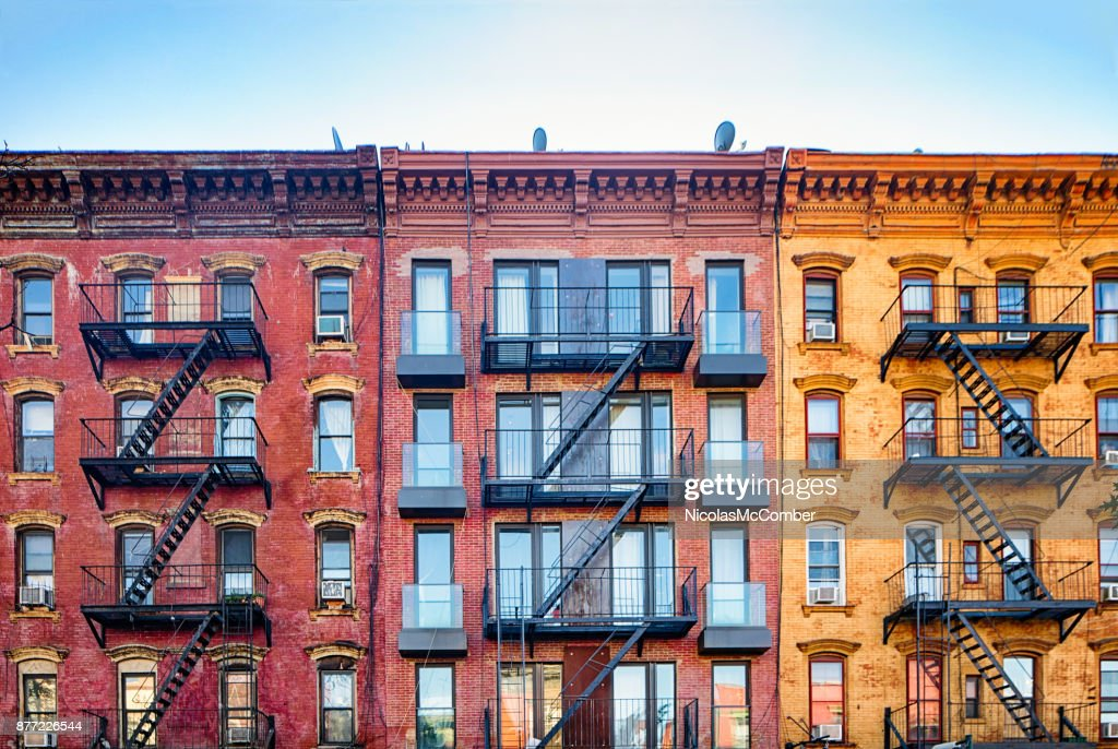 Top stories of colorful Williamsburg apartment buildings with steel fire escape stairways : Stock Photo