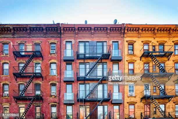 top stories of colorful williamsburg apartment buildings with steel fire escape stairways - new york stock pictures, royalty-free photos & images