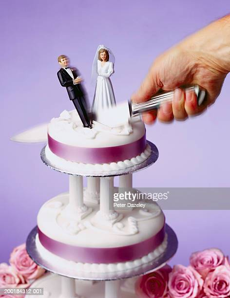 Top tier of wedding cake being cut, dividing model bride and groom