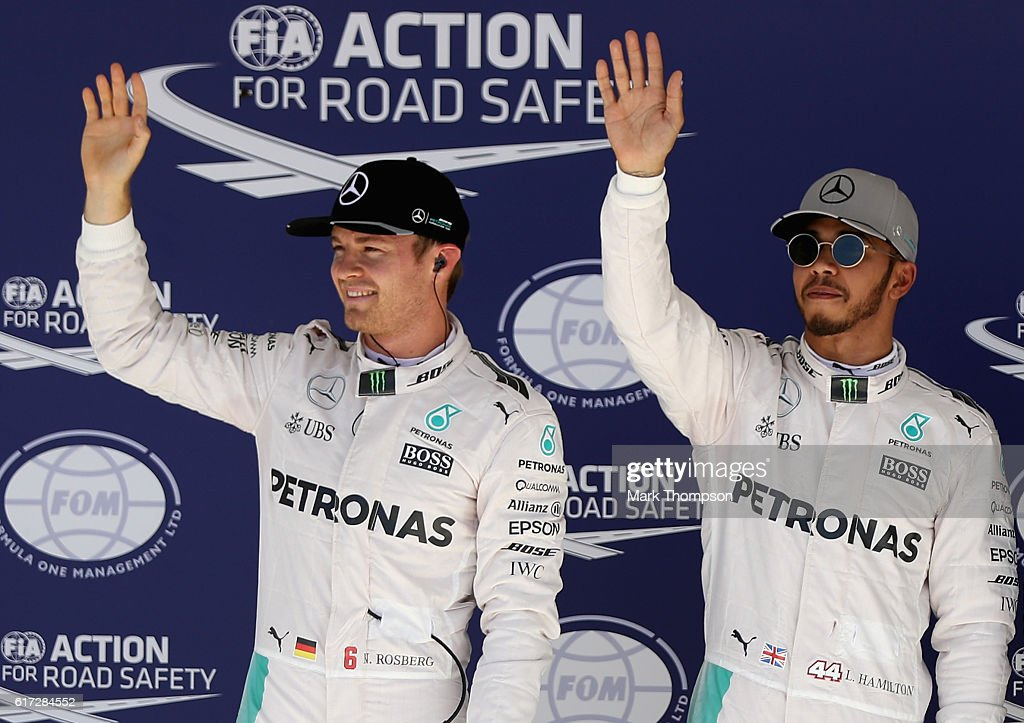 Top two qualifiers Nico Rosberg of Germany and Mercedes GP and Lewis Hamilton of Great Britain and Mercedes GP wave to the crowd in parc ferme during qualifying for the United States Formula One Grand Prix at Circuit of The Americas on October 22, 2016 in Austin, United States.