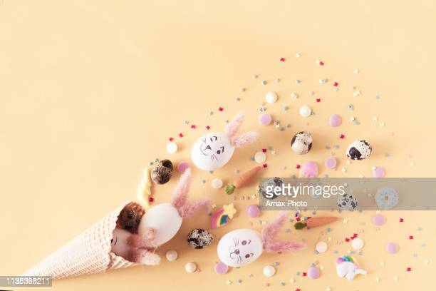 top view and flat lay of conceptual arrangement decoration for happy easter holiday on yellow background. colorful pastel eggs and topping spill out of the waffle horn with copy space. - pasqua foto e immagini stock