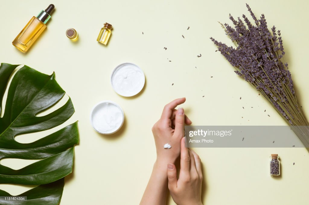 Top view and flat lay of woman holding cream on hands over white table with cosmetic products - avocado oil, cream and bamboo : Stock Photo