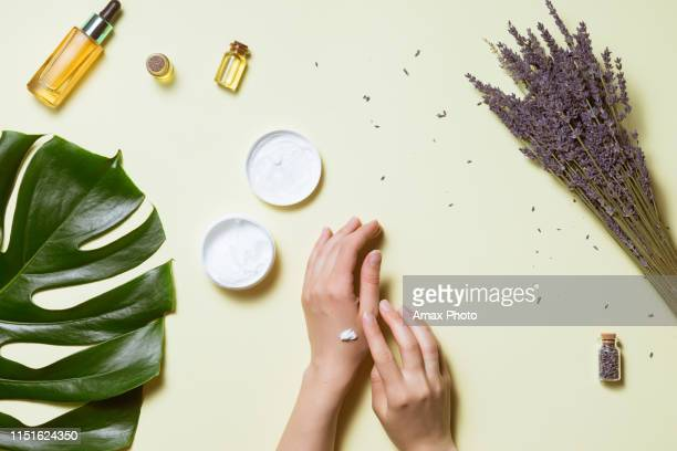 top view and flat lay of woman holding cream on hands over white table with cosmetic products - avocado oil, cream and bamboo - off white stock pictures, royalty-free photos & images