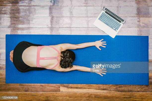 asian woman practicing yoga from home