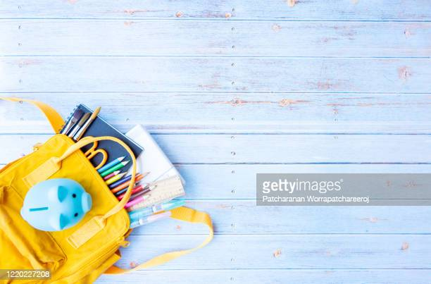 top view backpack with different colorful stationery and piggy bank on the wooden table with copy space. back to school concept - rucksack stock-fotos und bilder