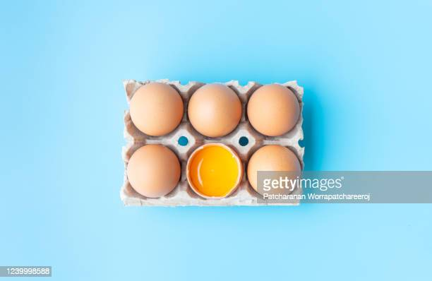 top view chicken eggs and broken egg half with a yolk  in carton box on blue background. - animal egg stock pictures, royalty-free photos & images