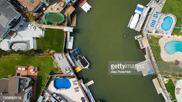 vista superior, directamente sobre fotos de drones de un canal en oceanside, nueva york, con casas con piscinas en patios traseros y muelles con barcos a lo largo de la costa. - queens fotografías e imágenes de stock