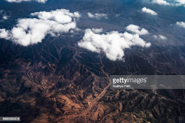 top view from airplane, beautiful view on the mountains from the top through the clouds. - topografische karte stock-fotos und bilder