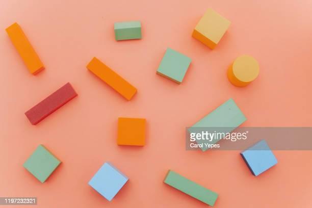 top view geometric shapes in coral background - blokken stockfoto's en -beelden