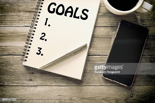 Top view goals list with notebook, cup of coffee on wooden desk