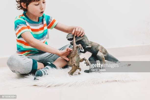 top view image of boy in pajama playing dinosaurs toys - dinosauro foto e immagini stock