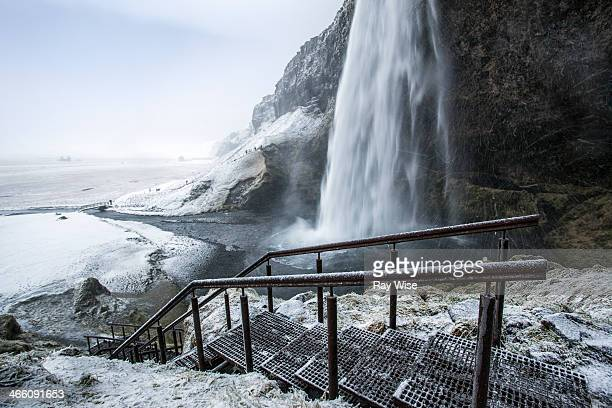 Top view looking over one of Icelands most famous waterfalls in the winter. An old metal staircase leads us into the frame with an icy landscape and...
