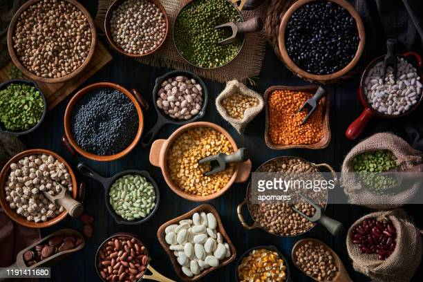top view low key of a large variety of dry beans. shot from above on rustic wooden table - legume family stock pictures, royalty-free photos & images