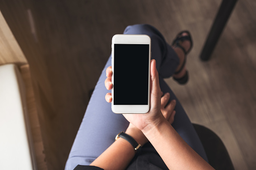 Top view mockup image of a woman holding white mobile phone with blank black desktop screen on thigh in cafe 943638824