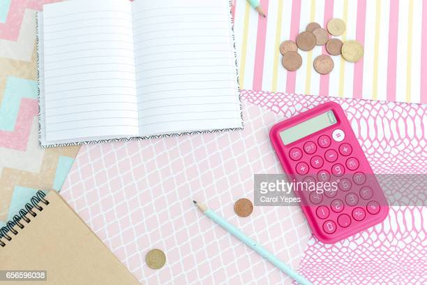 top view notebook, pencil, calculator and coins