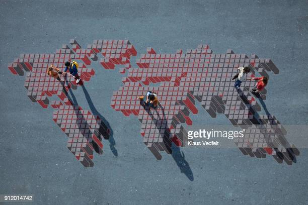 Top view of 3 pairs of people talking, while standing on world map, painted on asphalt