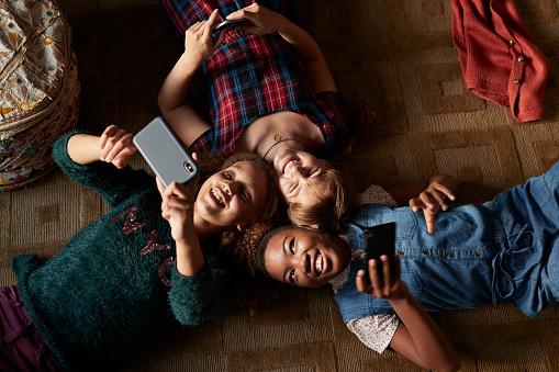Top view of 3 tween girls laughing and looking at their smartphones - gettyimageskorea