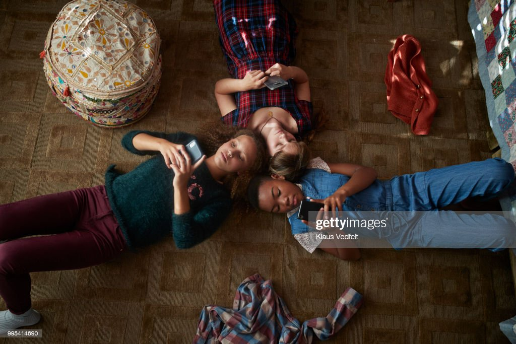 Top view of 3 tween girls looking at their smartphones : Stock Photo