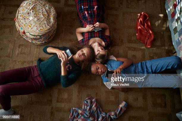 top view of 3 tween girls looking at their smartphones - bad bangs stock pictures, royalty-free photos & images