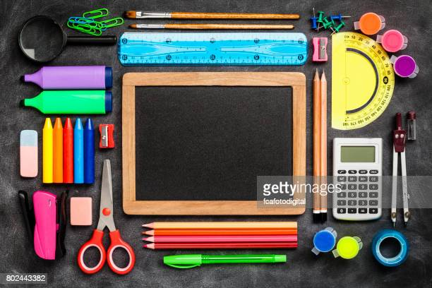 Top view of a blackboard with school supplies on black background