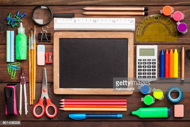Top view of a blackboard with school supplies on wooden table