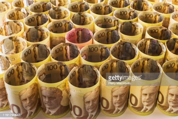 top view of a bunch of upright and rolled up canadian one hundred dollar banknotes - canadian one hundred dollar bill stock pictures, royalty-free photos & images