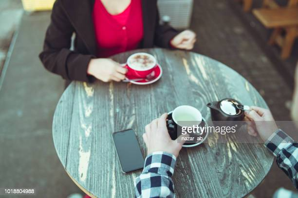 Top view of a couple having coffee outdoor.