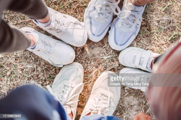 top view of a family of four wearing sneakers on lawn - witte schoen stockfoto's en -beelden