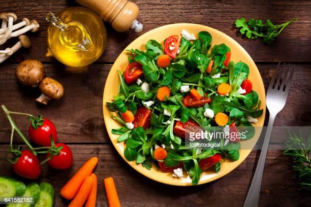 Vista superior de un plato de ensalada saludable en la mesa de madera rústica