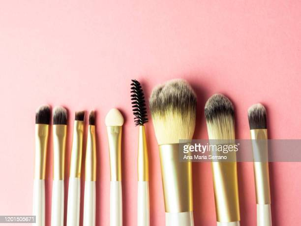 top view of a row of makeup brushes on a pink background - メイクアップブラシ ストックフォトと画像