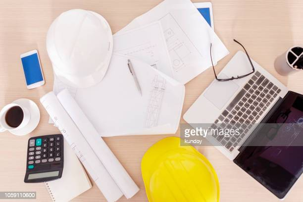 top view of a safety hat and construction accessories on the table with a roll of blueprint. - general stock-fotos und bilder