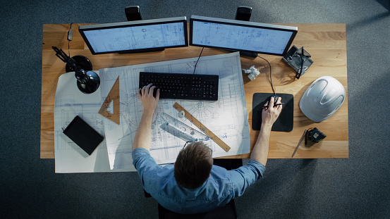Top View of a Technical Engineer Working on His Blueprints, Drawing Plans, Using Desktop Computer. Various Useful Items Lying on his Table. 971549280