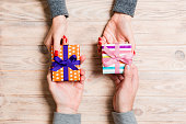 Top view of a woman and a man exchanging gifts on wooden background. Couple give presents to each other. Close up of making surprise for holiday concept
