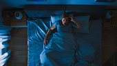Top View of a Young Man in Bed at Night Having Terrible Nightmare, He Wakes Up Scared and Covered in Sweat.