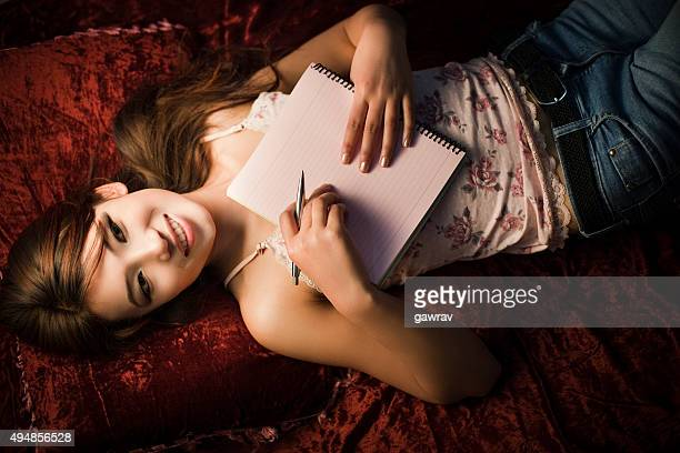 top view of asian girl laying down holding notepad, pen. - 18 19 years stock pictures, royalty-free photos & images