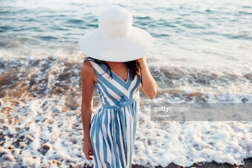 Top View Of Beautiful Woman With White Hat On Head Walking