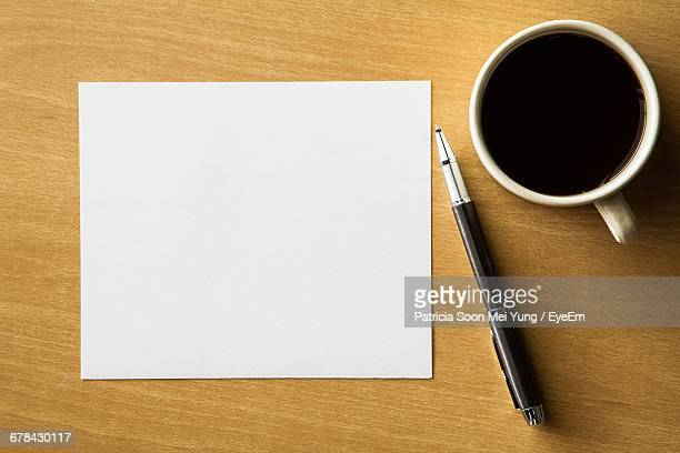 Top View Of Black Coffee With Blank Paper And Pen On Wooden Table