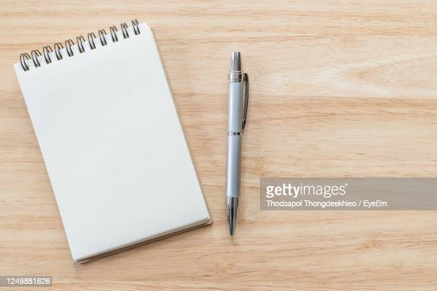 top view of blank notebook with pen and natural light on wooden table. - spirale photos et images de collection