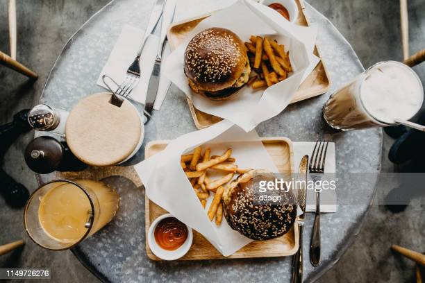 top view of burgers with french fries and drinks freshly served on table in cafe - gourmet stock pictures, royalty-free photos & images