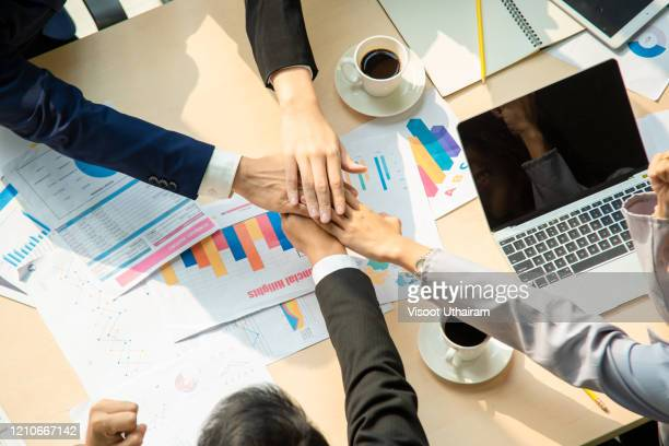 top view of business  people holding hands on top of one another in a symbol of unity while working in the creative office. - organised group stock pictures, royalty-free photos & images